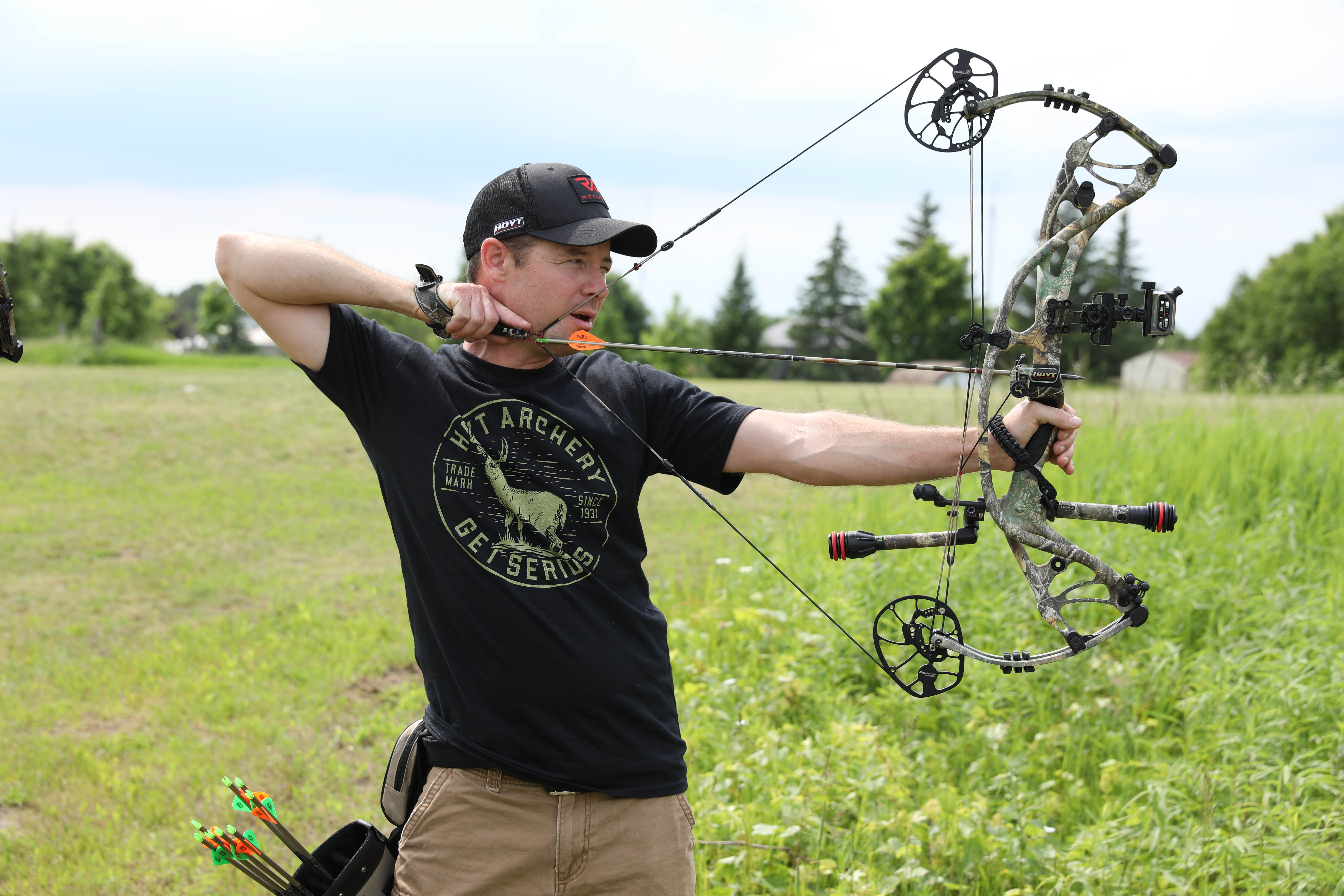 hunter with a compound bow reading a shot