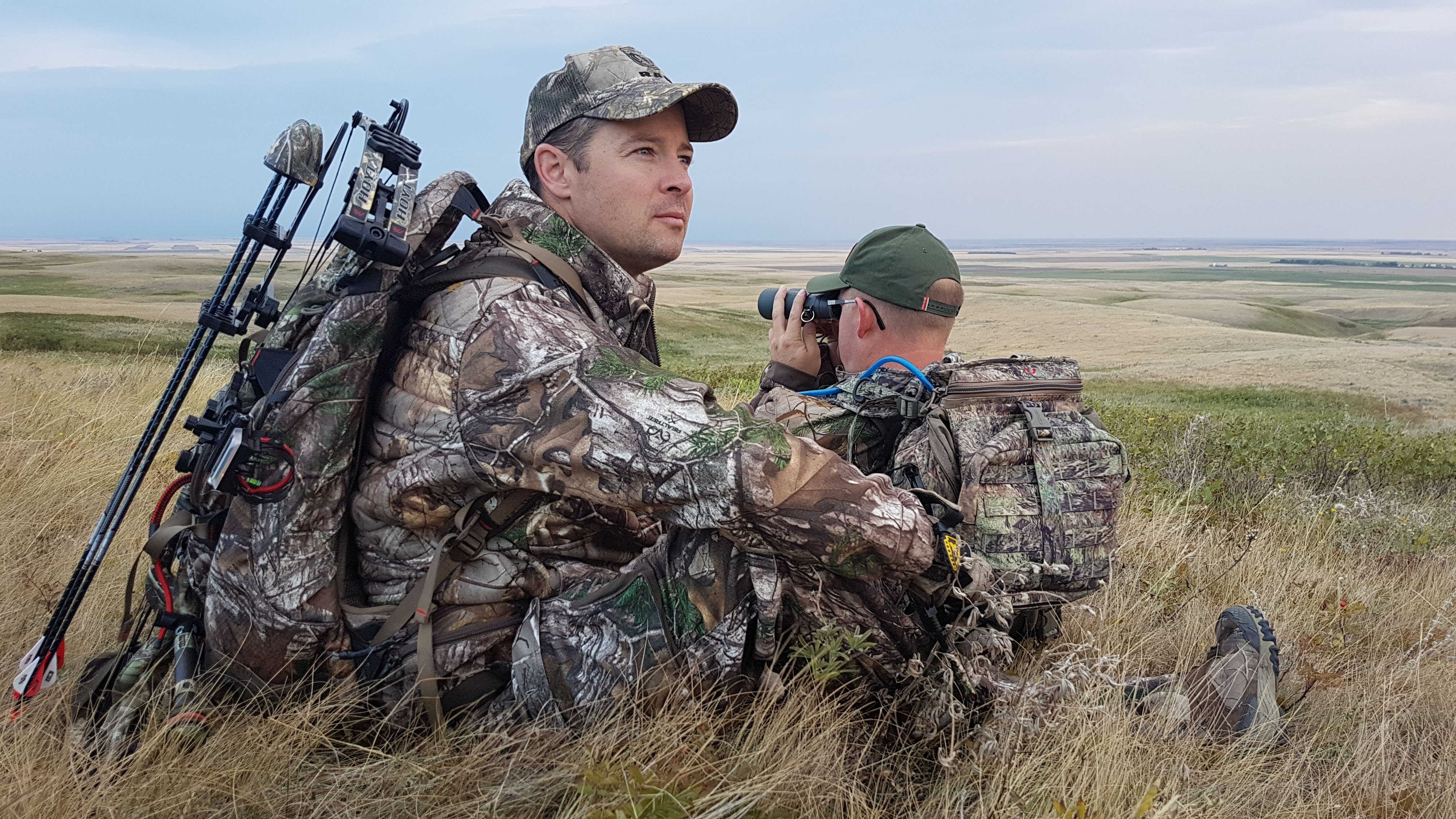 two hunters looking for game in grasslands