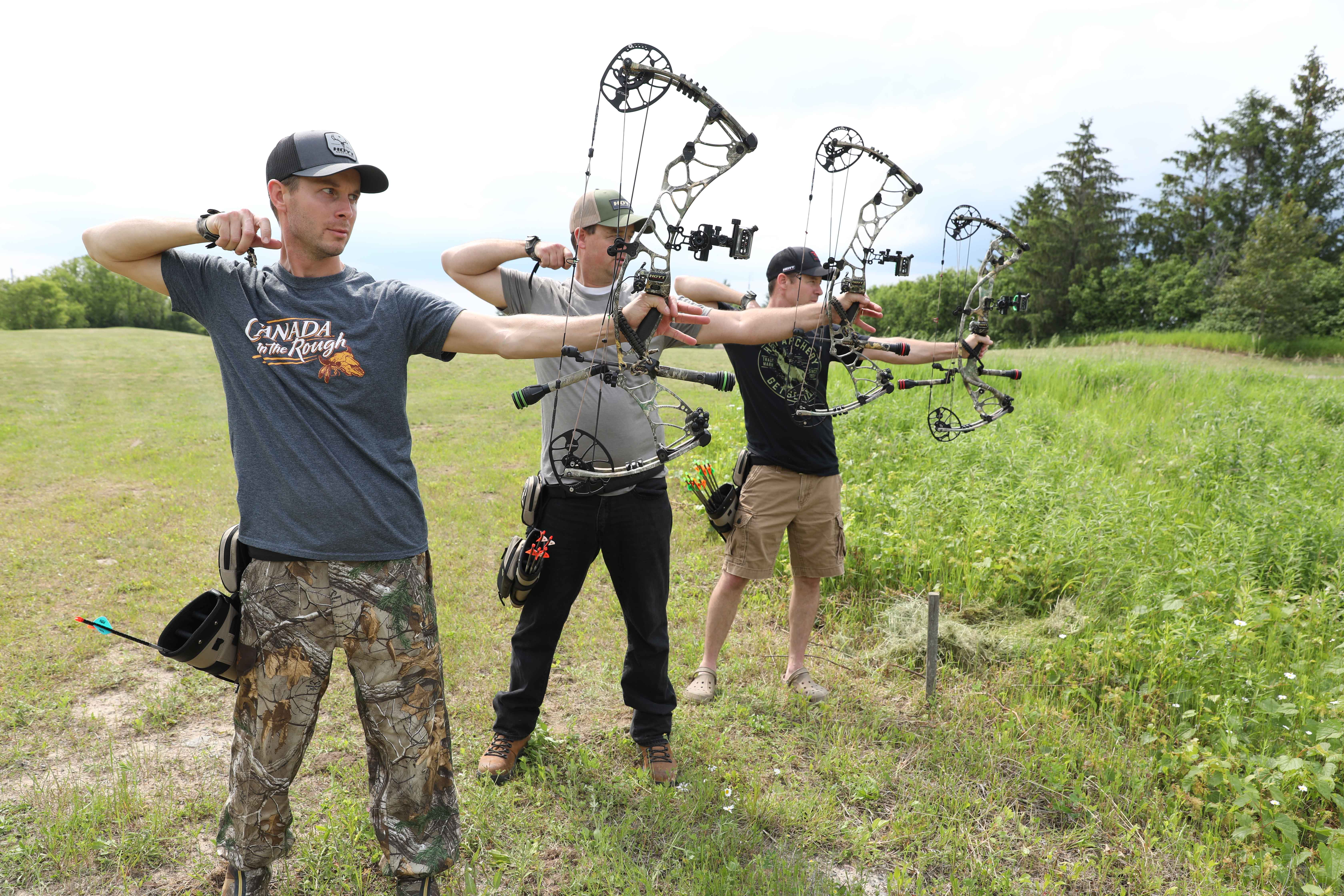 three hunters with compound bows